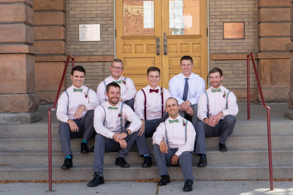 Groom and his groomsmen sitting on the steps at the Billings Depot