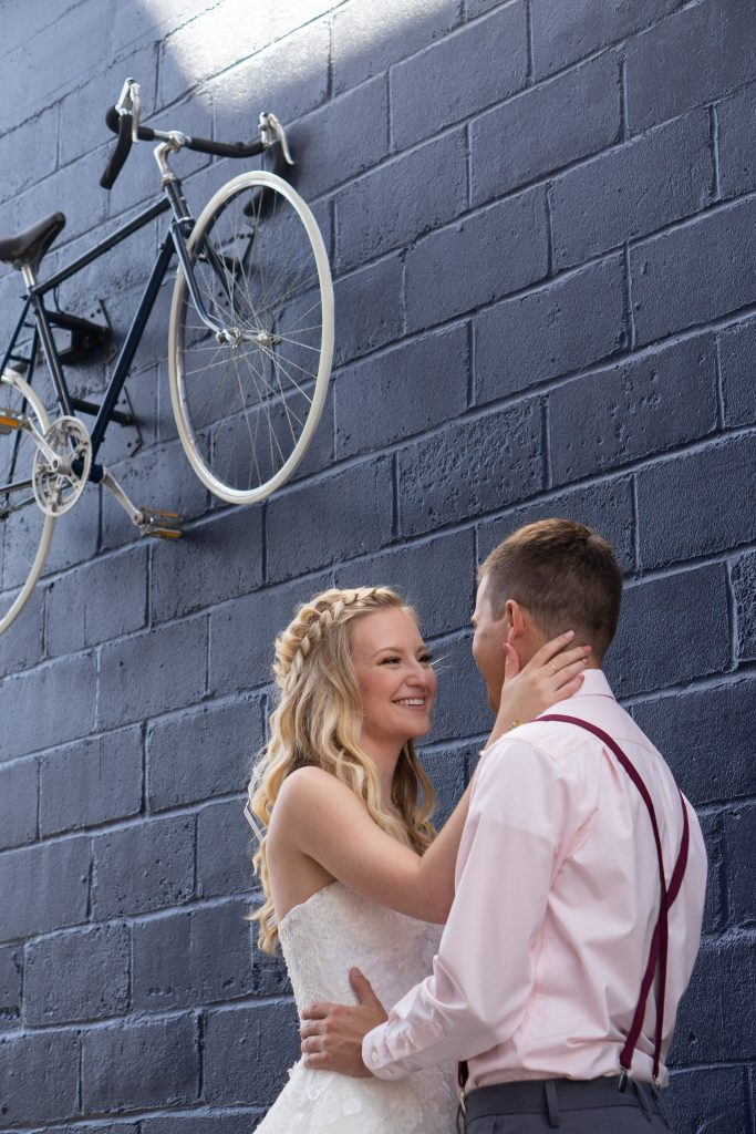 bride and groom standing against a dark blue wall