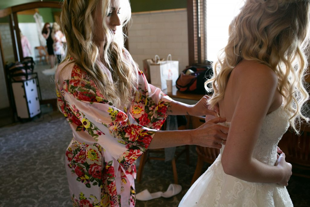 Brides mom helping her get into her dress